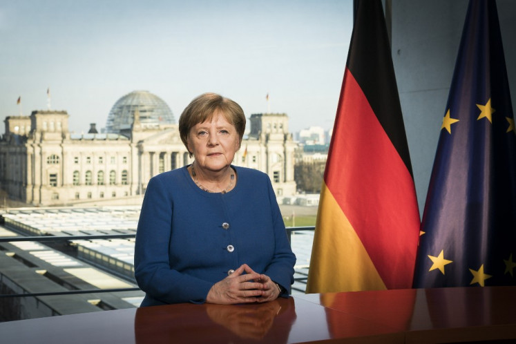 Germany's Merkel returns to office after quarantine stint