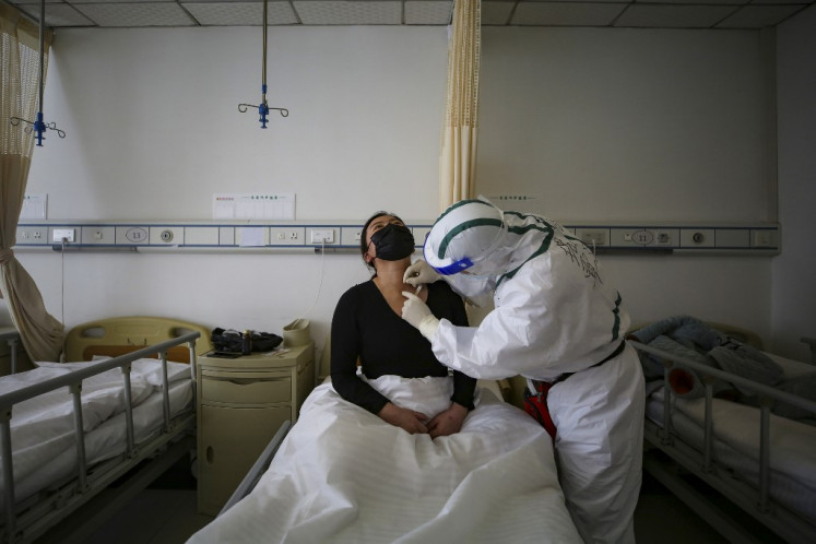 A patient (L) infected by the COVID-19 coronavirus receives acupuncture treatment at Red Cross Hospital in Wuhan in China's central Hubei province on March 11, 2020.
