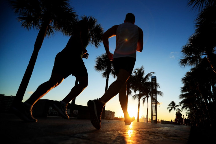 People exercise in South Pointe Park on March 18, 2020 in Miami Beach, Florida. Miami Beach city officials closed the area of the beach that is popular with college spring breakers and asked them to refrain from large gatherings where COVID-19 could spread.