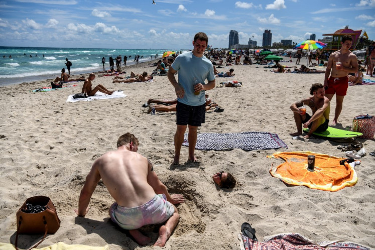 Tourists relax on the beach in Miami Beach, Florida, on March 18, 2020.