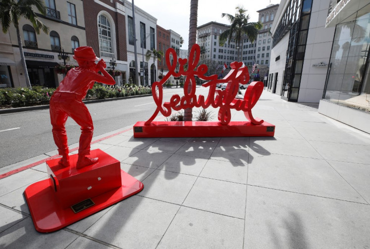 The sculpture 'Life is Beautiful' by Mr. Brainwash stands on iconic and nearly empty Rodeo Drive on March 18, 2020 in Beverly Hills, California. The city of Beverly Hills mandated the closure of non-essential stores, including the famous retailers on Rodeo Drive, starting today in response to the coronavirus (COVID-19) pandemic.
