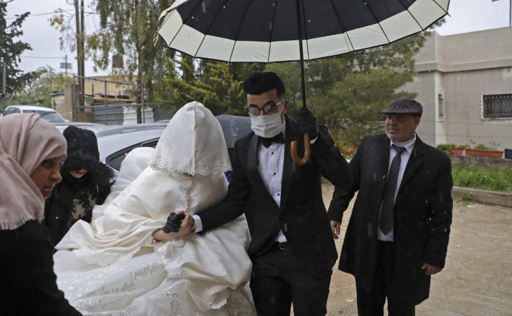 White dress and matching mask: Palestinians brave virus to wed