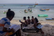 Children find a hand shade for reading their books at Mali Beach on Alor Island, East Nusa Tenggara. JP/ Yusuf Wahil