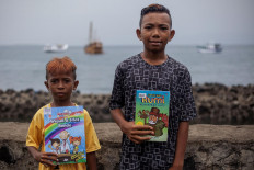 Two boys show the new books they received from an Armada Pustaka Mandar oral book review session at Waiwuring, East Flores. JP/ Yusuf Wahil
