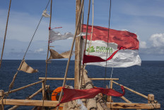 Sailing under the flag of Pustaka Bergerak Indonesia (Library in Motion), the Armada Pustaka Mandar program's padekawang floating library sails on the Flores Sea. JP/ Yusuf Wahil