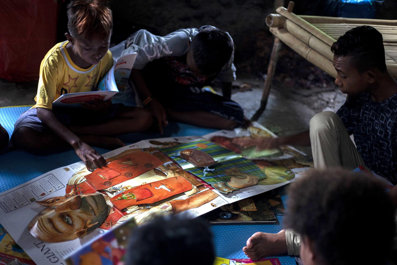 Children read a pop-up book during a literacy event in Waiwuring, East Flores. JP/ Yusuf Wahil