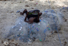 A boy lays atop a pile of fishing nets as he reads a book at Mali Beach on Alor Island, East Nusa Tenggara. JP/ Yusuf Wahil