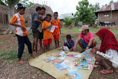 Muhammad Ridwan Alimuddi (second right), the founder of the Armada Pustaka Mandar program, watches as children select books from a mat on Pantar Island in East Nusa Tenggara. JP/ Yusuf Wahil