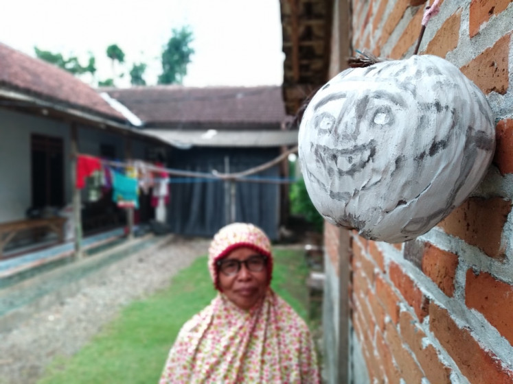 Yasmini, a Wajak Kidul villager in Tulungagung, East Java, looks at a 'tetek melek' mask fastened on the outer wall of her home. Some villagers put the masks around their houses in an effort to ward off the coronavirus.