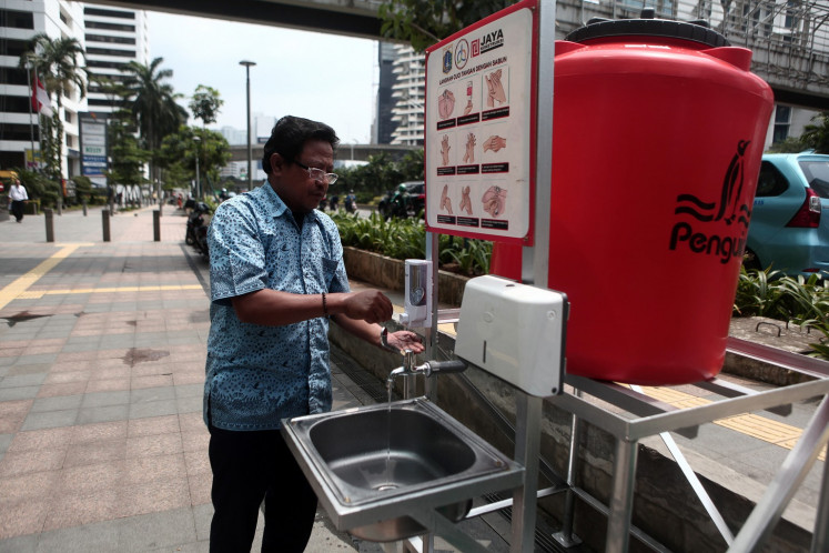 A taxi driver washes his hands at a temporary public sink on Jl. MH. Thamrin in Central Jakarta on March 24.