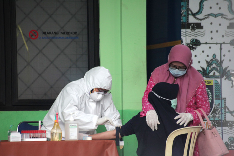 A mother comforts her daughter, who is undergoing a rapid test for COVID-19 at the Abadijaya community health center in Depok, West Java, on Friday. COVID-19 tests are being held in a number of community health centers in Depok.