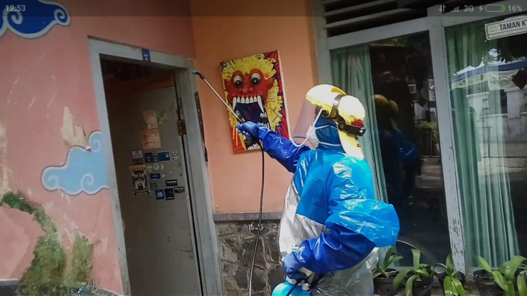 A resident of a kampung near Taman Sari Water Castle in Yogyakarta sprays disinfectant on a house on March 28, 2020.