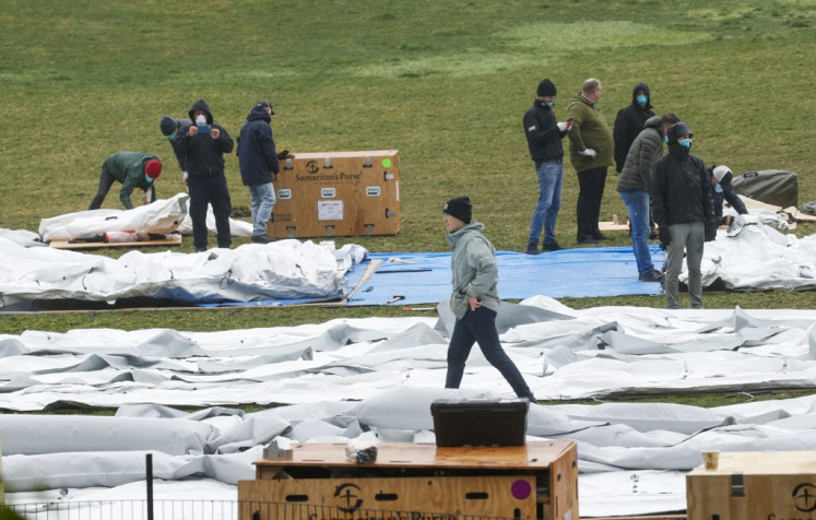 Workers set up a field hospital in front of Mount Sinai West Hospital inside Central Park on March 29, 2020 in New York City. - A senior US scientist issued a cautious prediction March 29, 2020 that the novel coronavirus could claim 100,000 to 200,000 lives in the United States. Dr. Anthony Fauci, who leads research into infectious diseases at the National Institutes of Health, told CNN that models predicting a million or more deaths were