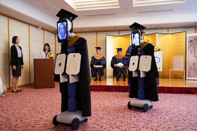 Ipads attached to 'newme' robots replacing graduating students' presence at a ceremony, wear graduation gowns and hats in Tokyo, Japan March 28, 2020.