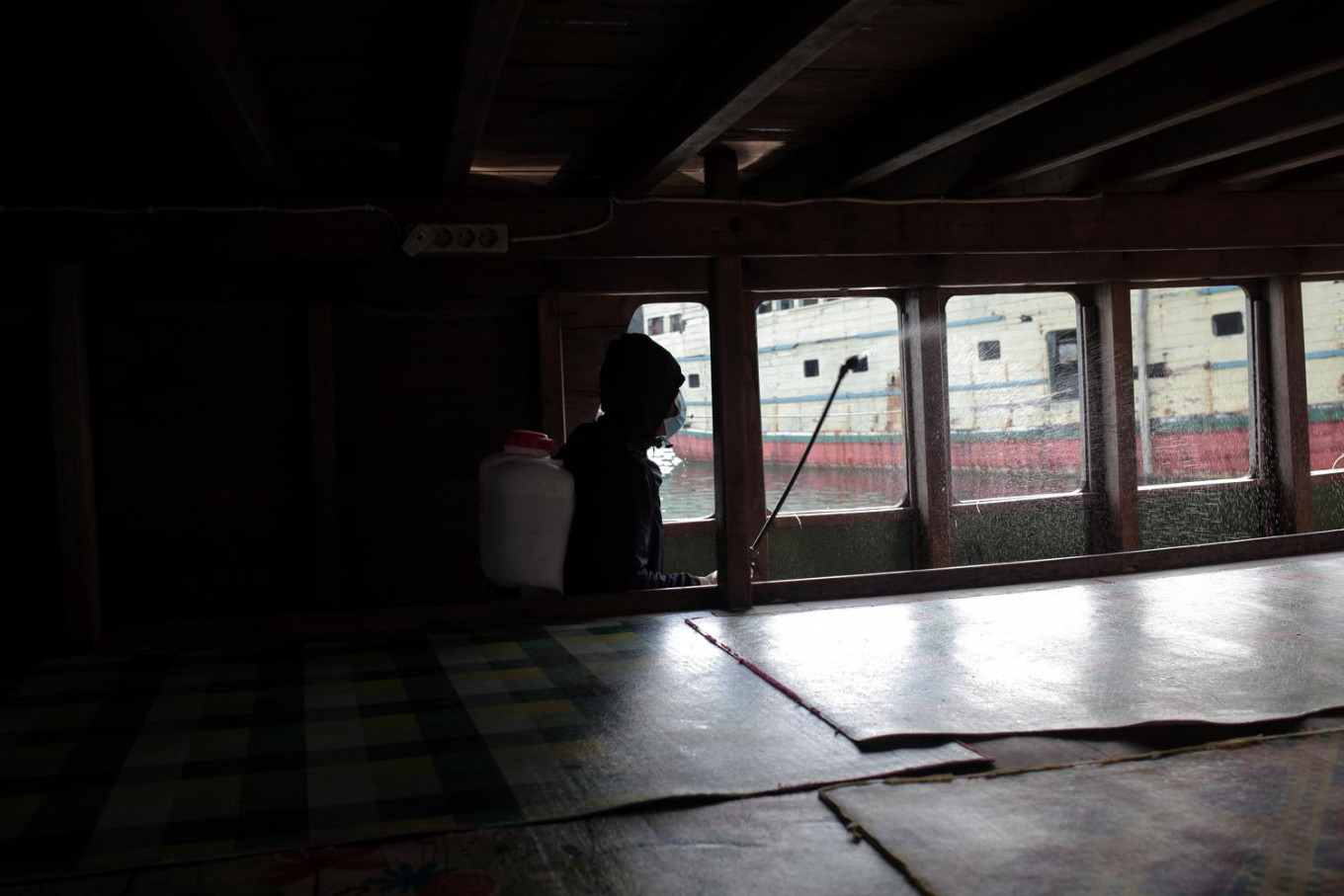 After all the passengers are cleared, a disinfectant worker sprays the boat's cabin. JP/ Edy Susanto