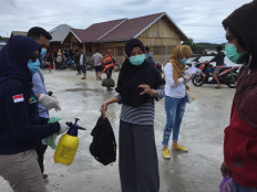 Health workers ask an arriving passenger to identify herself at Ambeua Port on Kaledupa Island. JP/ Edy Susanto
