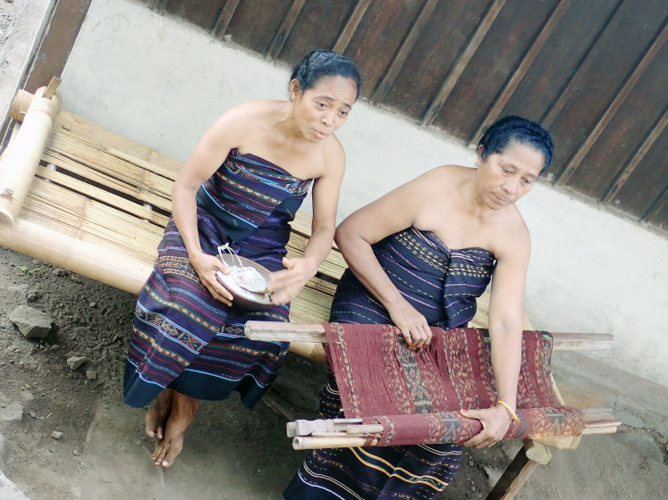 Intricate: Two weavers show a handwoven textile produced using the double ikat dyeing technique in Lembata, East Nusa Tenggara. Many weavers in the region are the breadwinners in their families.
