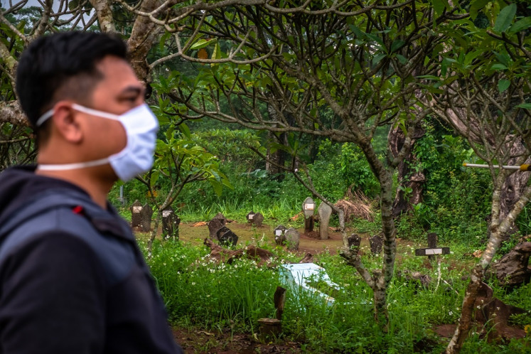 A local resident walks near Sasanalaya Girilayu public cemetery in West Ungaran, Semarang regency, Central Java on April 11, 2020. Semarang regency's COVID-19 task force has prepared a 3.4-hectare plot of land owned by the regency administration next to the cemetery as a burial site for deceased COVID-19 patients.