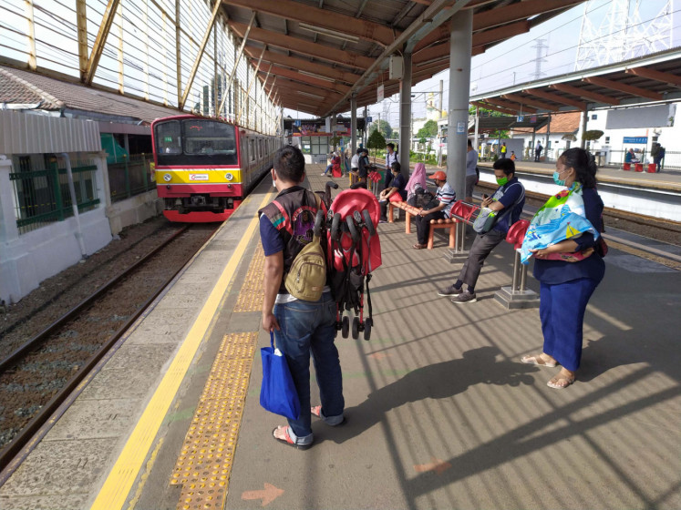 Passengers wait for a commuter train to arrive at Depok station in West Java on Monday, April 13. Under the large-scale social restrictions (PSSB) policy, the commuter train has limited its operational hours.