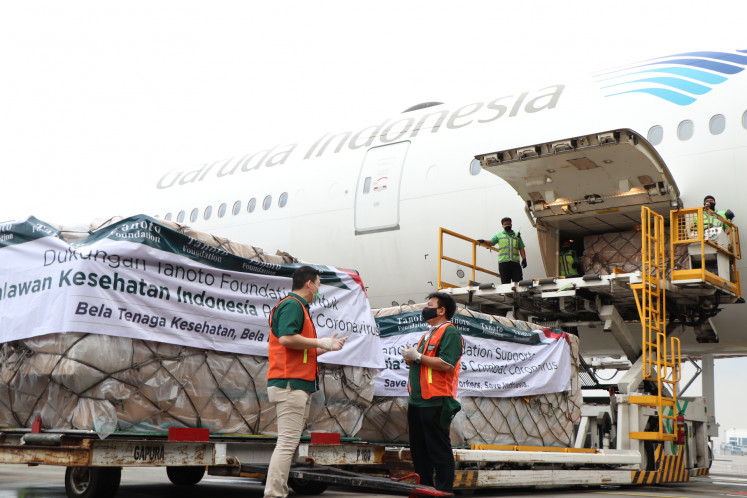 A Garuda Indonesia Boeing 777-300ER arrives at Soekarno-Hatta International Airport on April 13. The aircraft was chartered by the Tanoto Foundation to transport 30 tons of personal protective equipment for donation sourced from Shanghai, China. Tanoto Foundation COVID-19 Project Lead/ Head of ECED Eddy Henry (left) and foundation adviser Sihol Aritonang (right) were seen inspecting the cargo. The goods delivered are a portion of 1 million surgical masks, 1 million surgical gloves, 100,000 protective gowns and 3,000 goggles that the foundation is committed to donating to the National Disaster Mitigation Agency for distribution to COVID-19 referral hospitals in Jakarta, Medan and Pekanbaru.