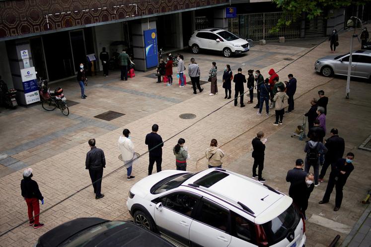 China mandates coronavirus tests for key workers leaving Wuhan