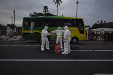 Disinfectant staff from the Yogyakarta administration prepare their sprayers before evacuating a man suspected of dying from COVID-19, at the zero kilometer area on March 30. JP/Arnold Simanjuntak