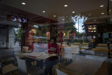 A restaurant employee finishes some paperwork among empty tables in Jl. Malioboro, Yogyakarta, on April 5. Some restaurants only serve take away, while many food stalls have decided to shut down. JP/ Arnold Simanjuntak