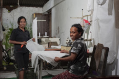 Sri Mulyani, 45, and Sri Suparmi, 31, sew hazmat suits at their home in Wedomartani village, Sleman, on April 1. The two help a community of disabled tailors to finish the suits, which are urgently needed by a local hospital. JP/ Arnold Simanjuntak