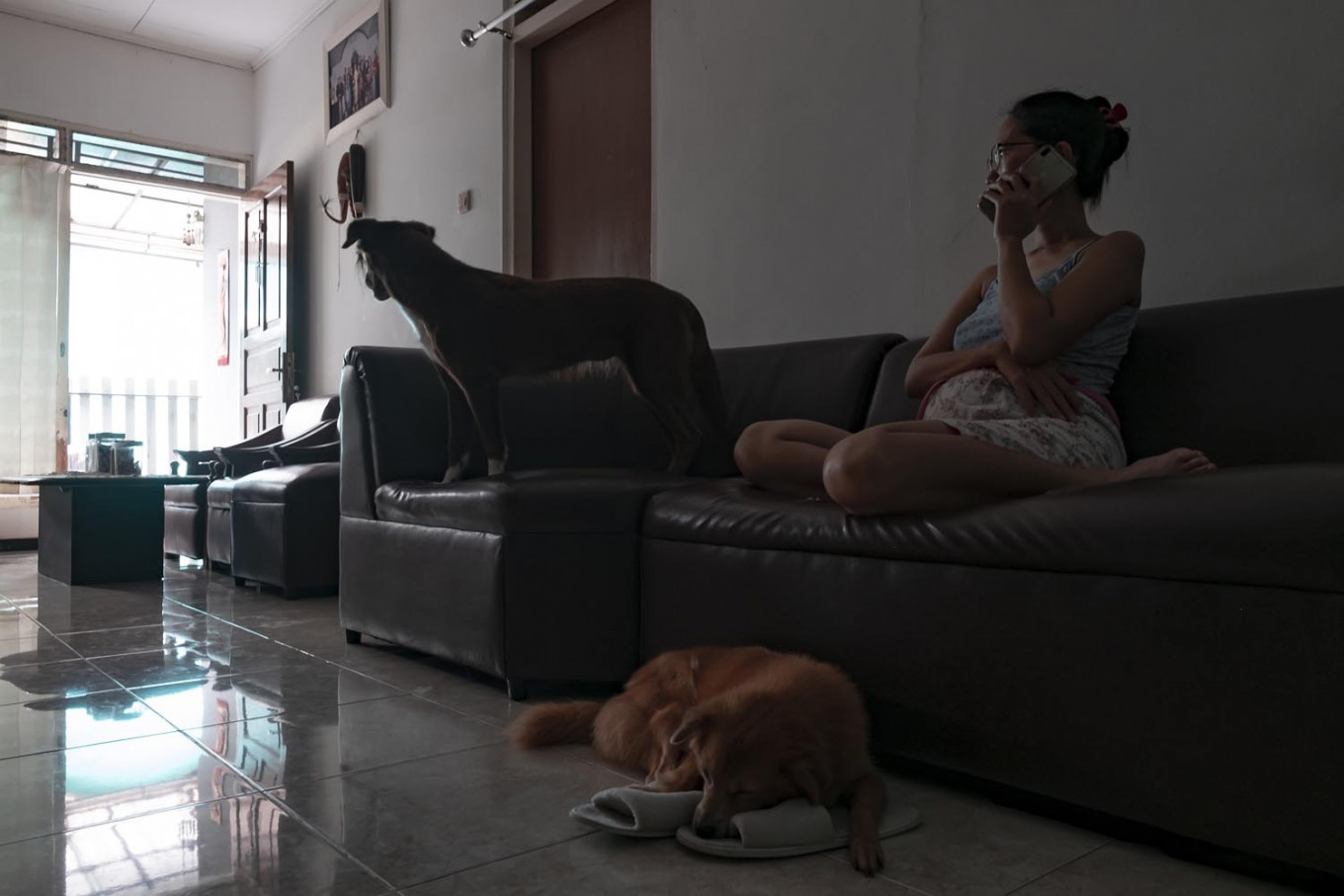 Astri Suryani, a manager at a private company, arranges the salary payments of employees through a phone call at her home in Yogyakarta on April 3. JP/Arnold Simanjuntak