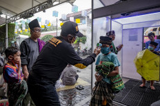 Worshippers walk through the disinfectant chamber and have their temperatures checked before Friday prayers at Jogokariyah Mosque in Yogyakarta on April 3. Some people keep going to mosques, although the government has called on people to pray at home. JP/Arnold Simanjuntak
