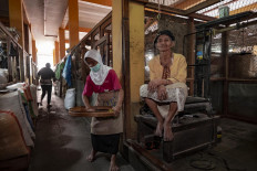 Rubiyem (right), a 70-year-old porter, sits at the corner of Bringharjo Market on April 6. She usually gets a daily income of Rp. 20,000 (US$ 1.26) for carrying produce with a total weight of 50 kilograms. She works seven days a week and does not have a mask to protect herself from COVID-19.  JP/Arnold Simanjuntak