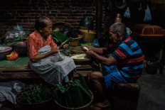 Satinem (left) and her husband Narto Utomo fill dozens of banana leaf tubes with glutinous rice. JP/Anggertimur Lanang Tinarbuko