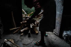 Satinem and her husband collect firewood to cook lupis. JP/Anggertimur Lanang Tinarbuko