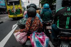 Mukinem and Satinem return to their home by motorcycle.  JP/Anggertimur Lanang Tinarbuko