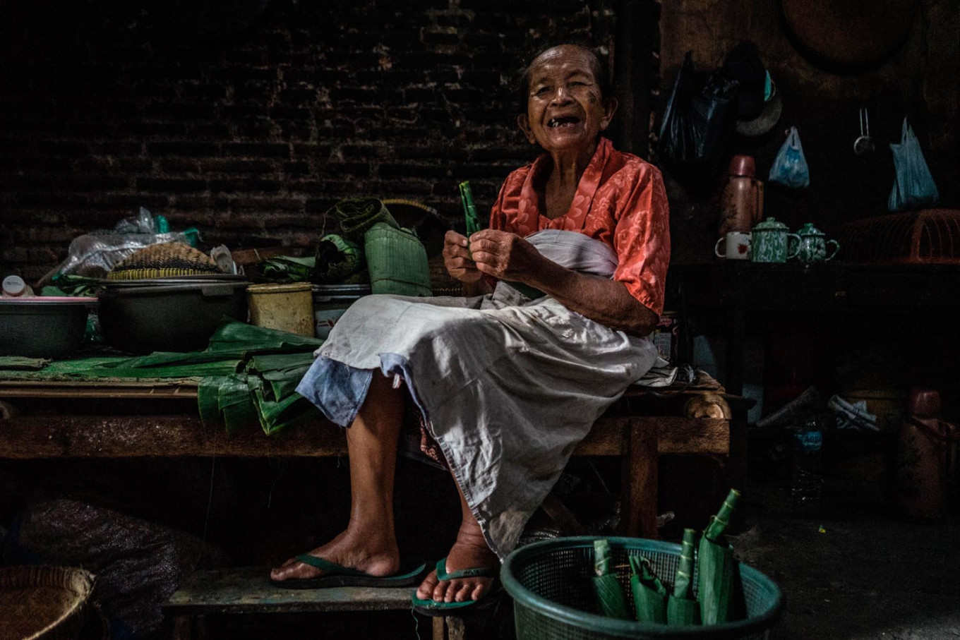 Satinem prepares to cook lupis, a traditional sweet snack. She forms a tube from a banana leaf, which will later be filled with glutinous rice. JP/Anggertimur Lanang Tinarbuko