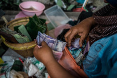 Satinem's daughter, Mukinem, calculates the money they've earned after finishing selling lupis with her mother. JP/ Anggertimur Lanang Tinarbuko