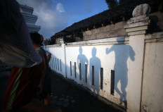 The shadow on the mosque's outer wall shows three boys making their way to the pool. JP/Boy T Harjanto