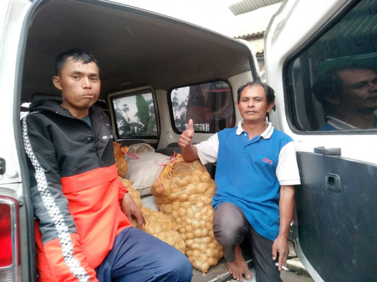 Asep Sutiandi (right) and a fellow farmer, who are members of the Pasundan Farmers Association, pose near potatoes that will be sent to a collective barn as part of the Agrarian Barn Movement organized by the association. The movement has proven useful during the pandemic.