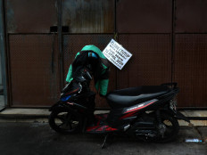 An ojek (motorcycle taxi) is parked in front of a closed shop in Green Ville housing complex in Tanjung Duren, West Jakarta. Many stores in the area have closed indefinitely following the coronavirus outbreak in the capital. JP/Sutrisno Jambul
