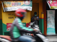 An online ojek driver drives past a kiosk in Kemanggisan, West Jakarta. Customers often share their food takeout with the driver as a tip.  JP/Sutrisno Jambul