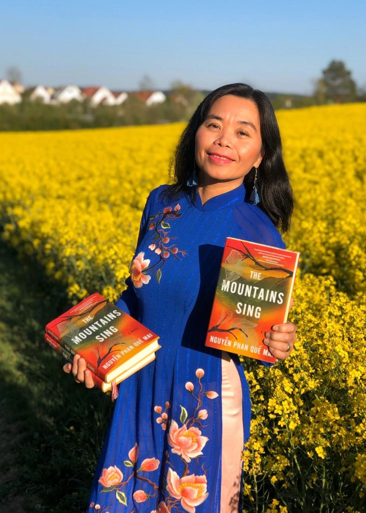 This handout picture taken on April 27, 2020 and released to AFP on April 29 by Vietnamese author Nguyen Phan Que Mai shows the writer posing for a photograph with copies of her novel 'The Mountains Sing' in Pfaffenhofen, Germany.