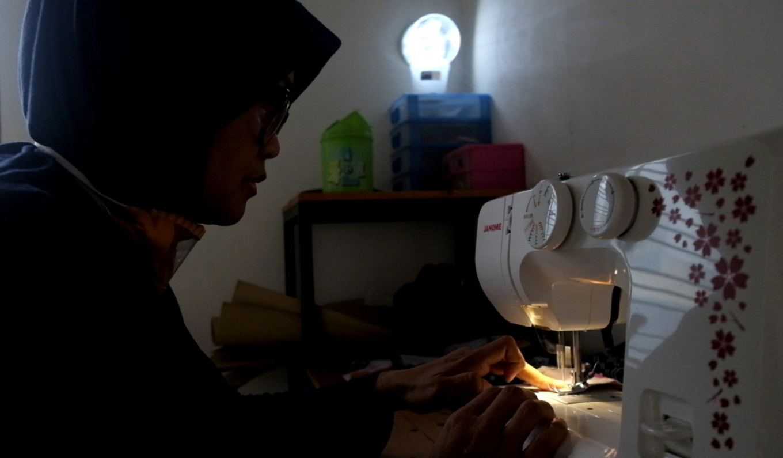 Dwi uses an electric sewing machine to make her transparent masks. JP/Arnold Simanjuntak
