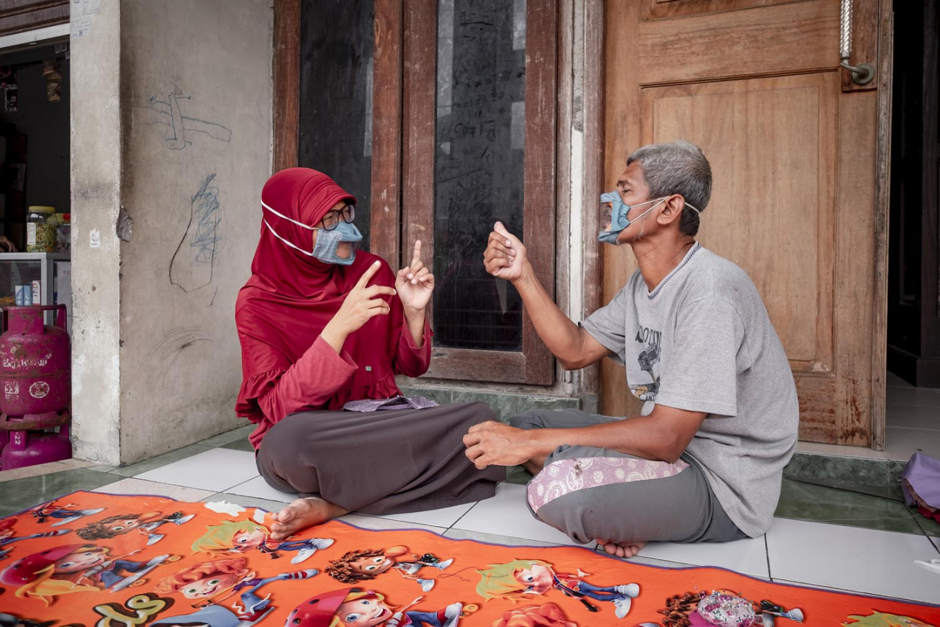 Dwi and her husband Elfiandi wear clear masks while chatting in front of their home. JP/Arnold Simanjuntak
