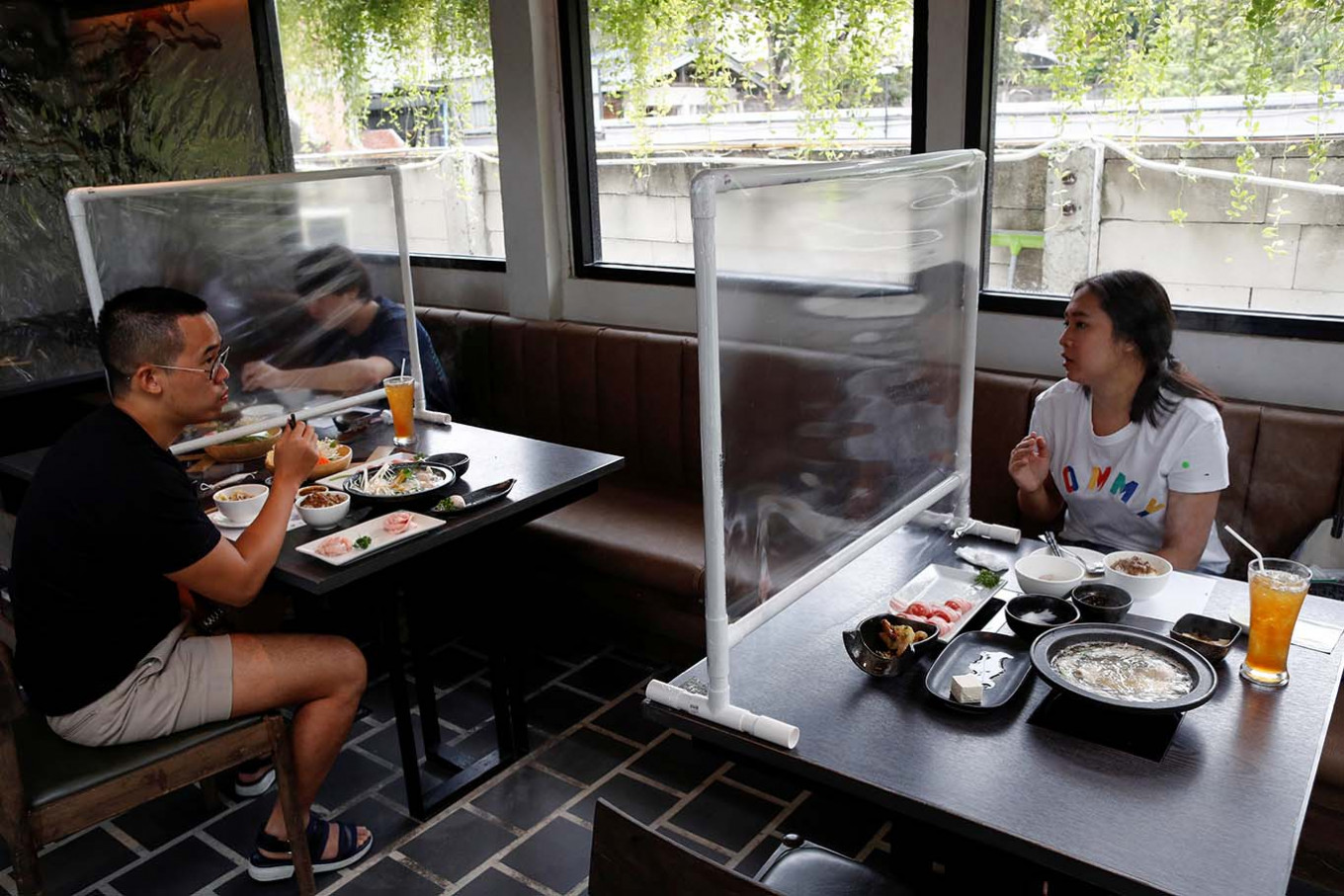 Bangkok reopens with stylists in scrubs, plastic screens between diners