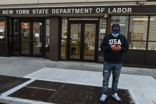 Luis Mora stands in front of the closed offices of the New York State Department of Labor on May 7, 2020 in the Brooklyn borough in New York City. 3.2 million Americans have filed for unemployment insurance this week bringing the total number of workers who have applied for aid to 33 million in the past two months.