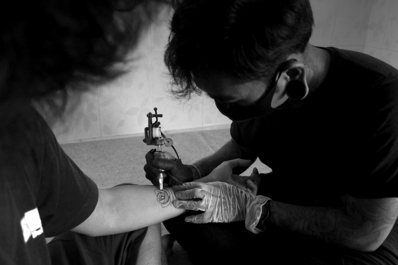 Kadek draws a pattern on the arm of a customer. JP/M Azis Dicky