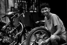 Imam installs parts of a wheel at his workshop in Bali.  JP/M Azis Dicky