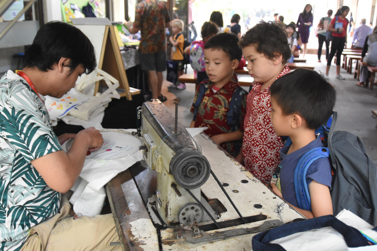 Spirit of stitching: With the help of a machine-embroidery artist, young artists at JIS' Pattimura elementary school campus create various items for sale, such as tote bags, pillow covers and small pillow ornaments that they designed themselves.