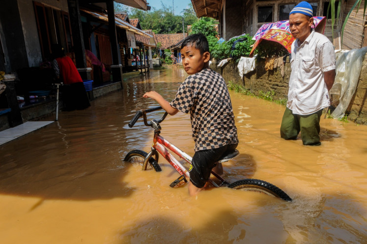 A child plays with his bicycle at the flooded Gubukan Cibereum village in Lebak, Banten on Thursday, May 14, 2020. Floodwater from the overflowed Cibereum River has inundated the village since Wednesday evening.