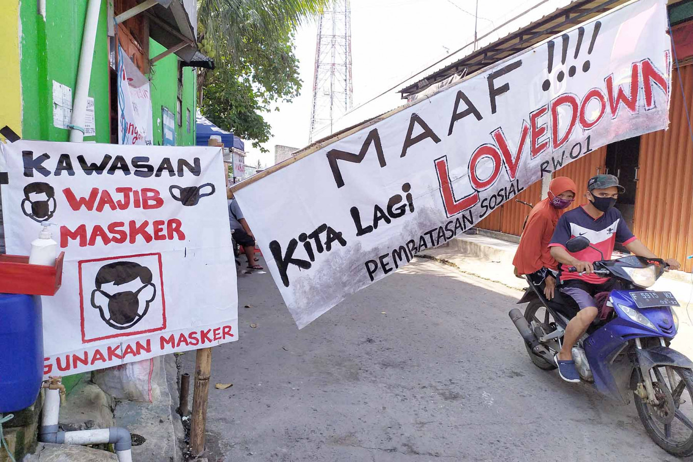 "A couple on motorcycle drive past a makeshift gate in a residential area in Citeureup, Bogor, West Java, on May 7. The gate displays a banner declaring a ""lovedown"" instead of a lockdown. JP/P.J. Leo"